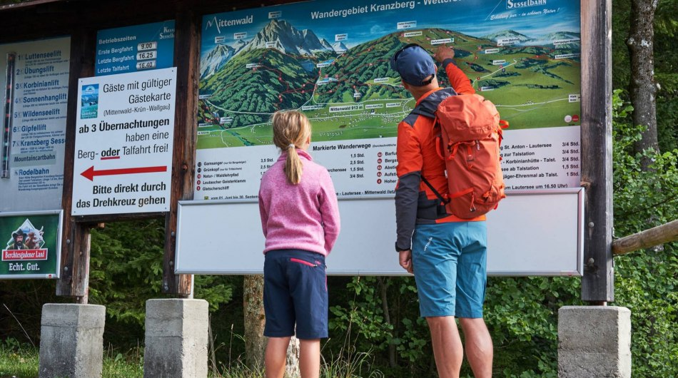 A family in front of the trail board in the hikingarea of Kranzberg near Mittenwald , © Alpenwelt Karwendel | Anton Brey