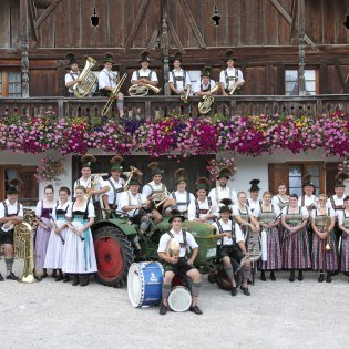 Portrait of the music band Krün in front of the farmhouse, © Alpenwelt Karwendel | Christoph Schober