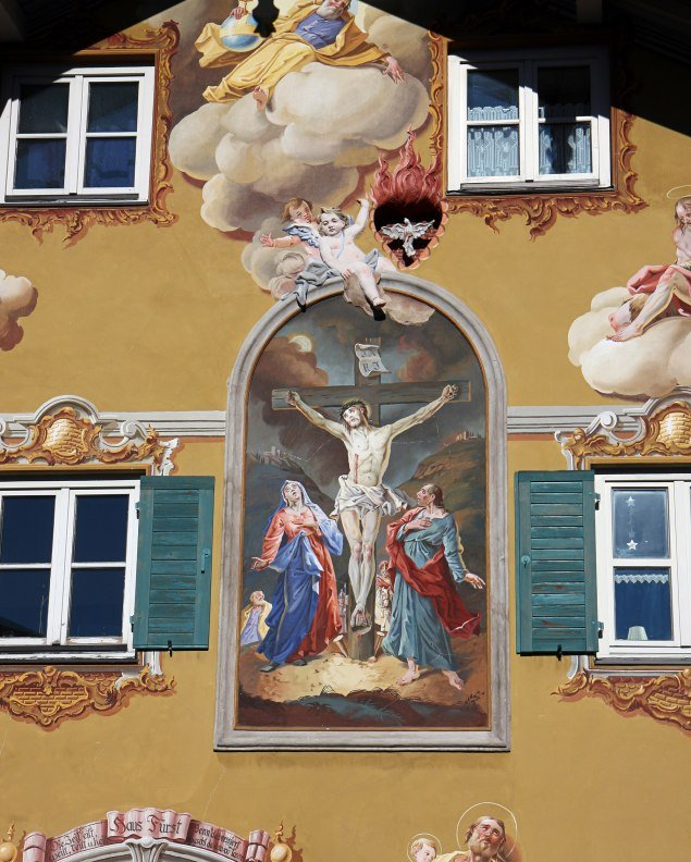 Fresco painting on a house in Mittenwald with Jesus on the cross in a passion representation. , © Alpenwelt Karwendel | Rudolf Pohmann